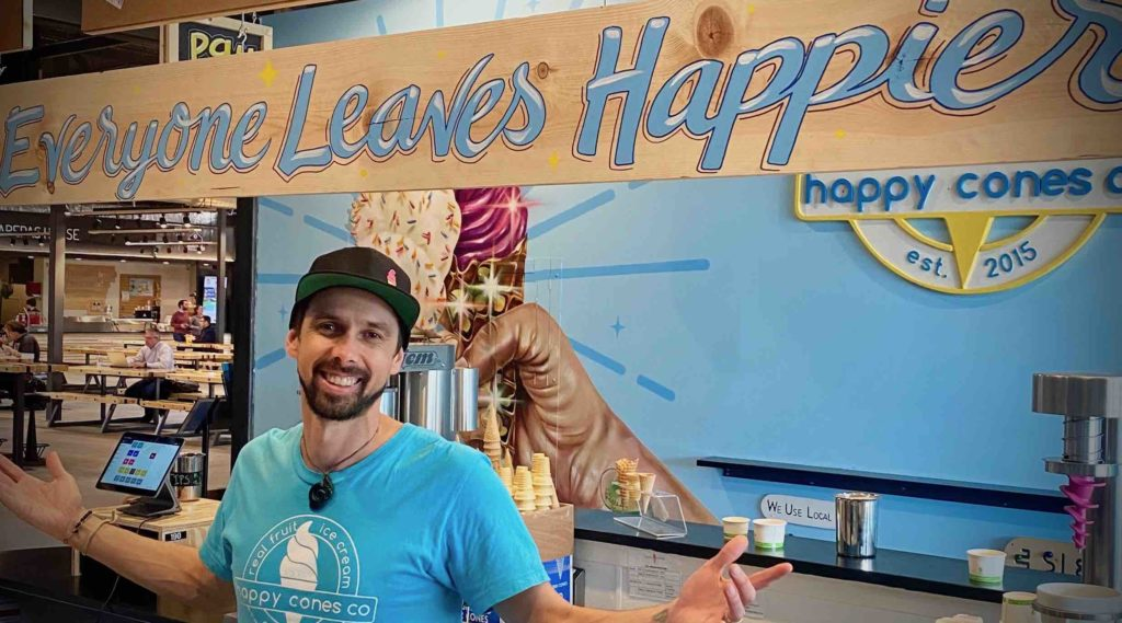 "Hap with ""Everyone Leaves Happier"" Sign in Edgewater Happy Cones Co ice cream shop"